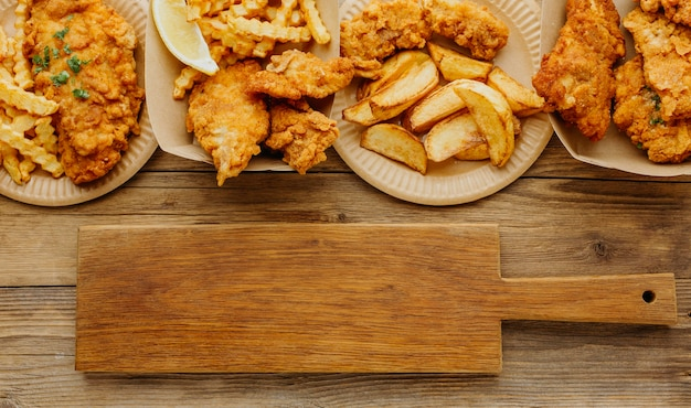 Vista superior de pescado y patatas fritas con tabla de cortar