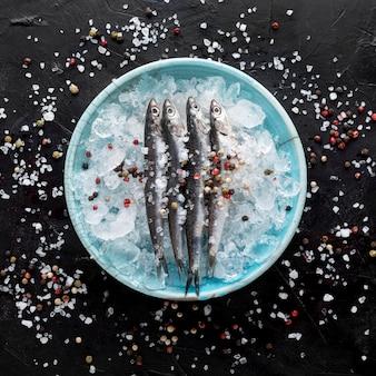 Vista superior de pescado en plato con hielo y especias