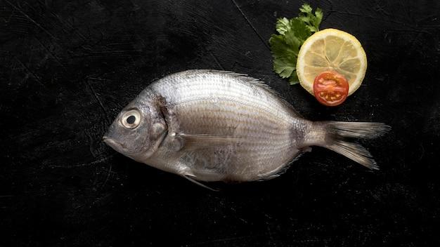 Vista superior de pescado con rodaja de limón y tomate