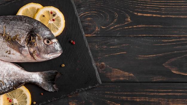 Vista superior de pescado y rodajas de limón.