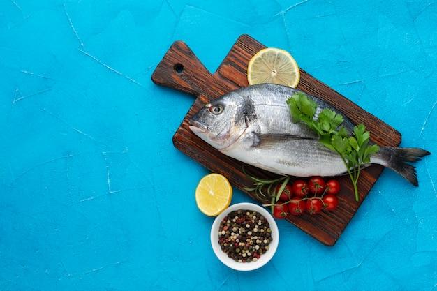 Vista superior de pescado sobre fondo de madera con condimentos