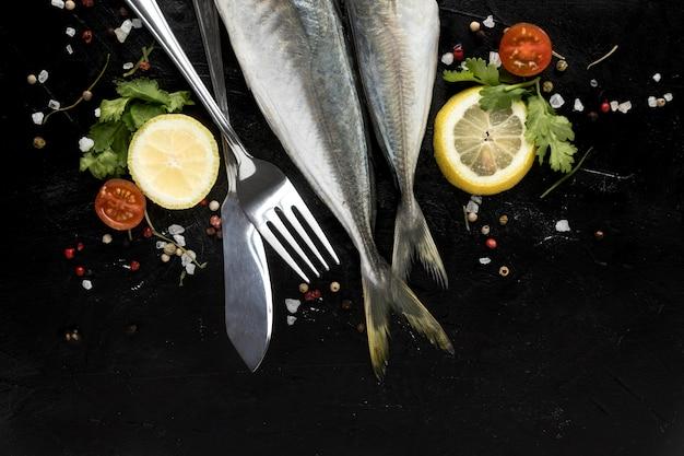 Vista superior de pescado con tomates y rodajas de limón.
