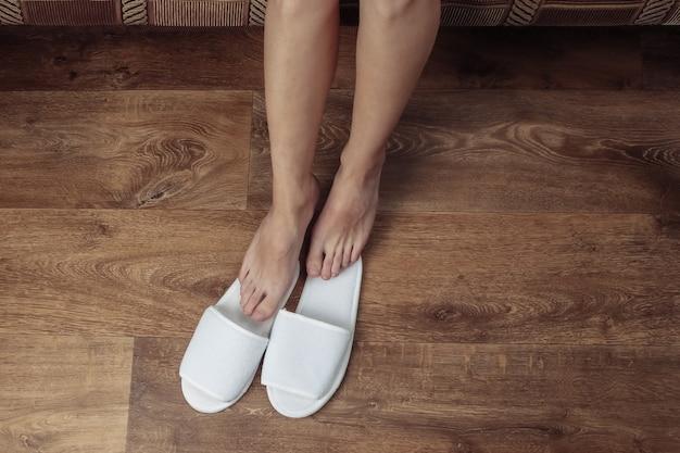 Vista superior de las piernas desnudas femeninas con zapatillas blancas sobre un piso de madera.