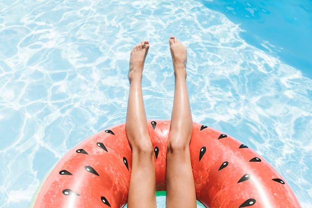 Vista superior de las piernas sobre el agua cristalina