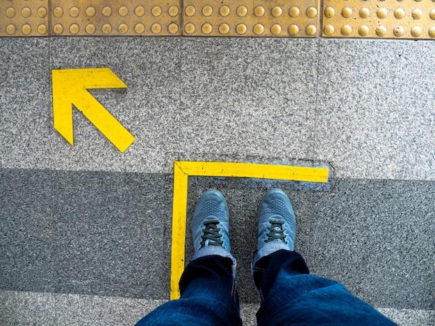 Vista superior de los pies del hombre que se colocan sobre símbolo de la flecha en la plataforma del subterráneo.