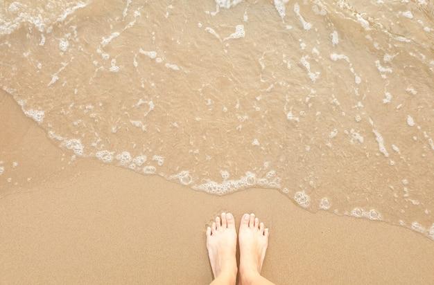 Vista superior de pies en la playa.