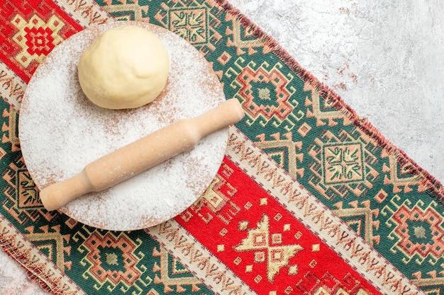 Vista superior de la pieza de masa cruda con harina en la alfombra colorida y harina de fondo blanco para hornear masa
