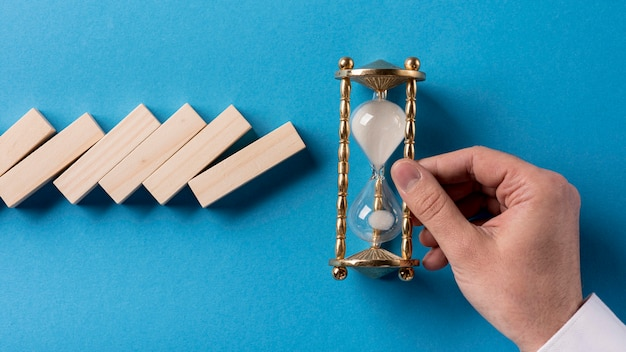 Vista superior de piezas de dominó con empresario sosteniendo reloj de arena