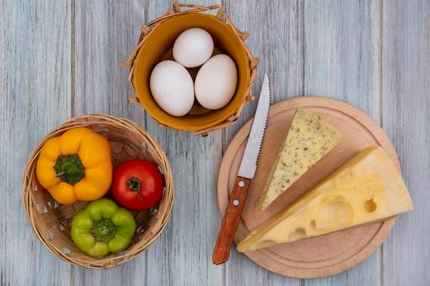 Vista superior de piezas de queso holandés con un cuchillo en un soporte con pimientos y huevos de gallina sobre un fondo gris