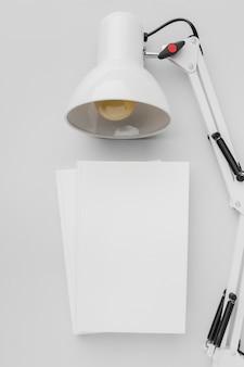 Vista superior pila de libros con lámpara