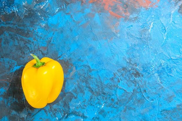 Vista superior del pimiento amarillo sobre superficie azul