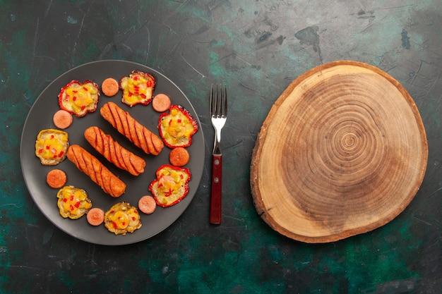Vista superior de pimientos cocidos con salchichas y escritorio de madera
