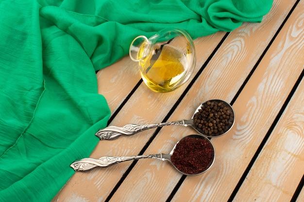 Vista superior de pimientos dentro de cucharas de plata y junto con aceite de oliva en el fondo de madera marrón