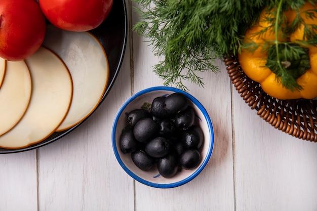 Vista superior de pimientos con eneldo en una canasta con aceitunas, queso ahumado y tomates sobre un fondo blanco.
