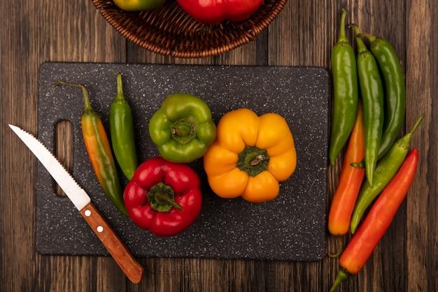 Vista superior de pimientos nutricionales en una placa de cocina negra con cuchillo con pimientos aislado sobre una superficie de madera