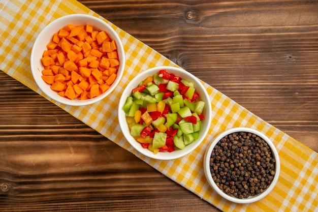 Vista superior de pimientos en rodajas con condimentos en la mesa de madera marrón verduras comida comida saludable ensalada