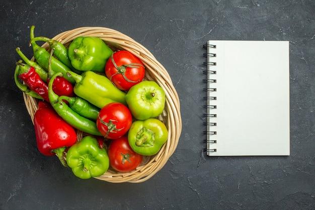 Vista superior de pimientos y tomates en un cuenco de cesta de mimbre un cuaderno sobre una superficie oscura