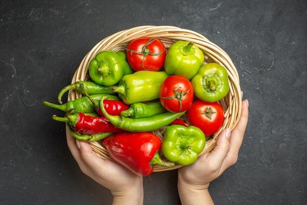 Vista superior de pimientos y tomates en un recipiente de cesta de mimbre en mano femenina sobre superficie oscura