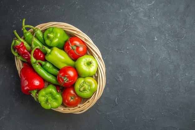 Vista superior de pimientos y tomates en un recipiente de mimbre en el espacio libre de la superficie oscura
