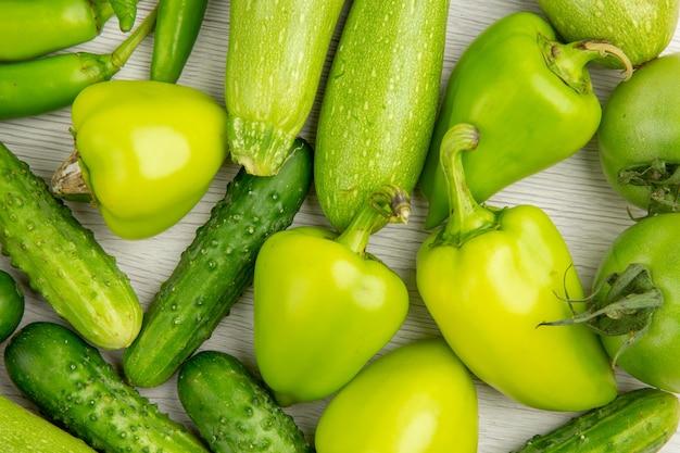 Vista superior de pimientos verdes frescos con pepinos verdes y tomates en el escritorio blanco comida de ensalada madura de color caliente