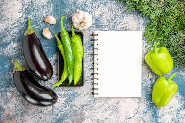 Vista superior de pimientos verdes en placa negra, berenjenas de ajo, pimientos, un cuaderno sobre fondo azul-blanco