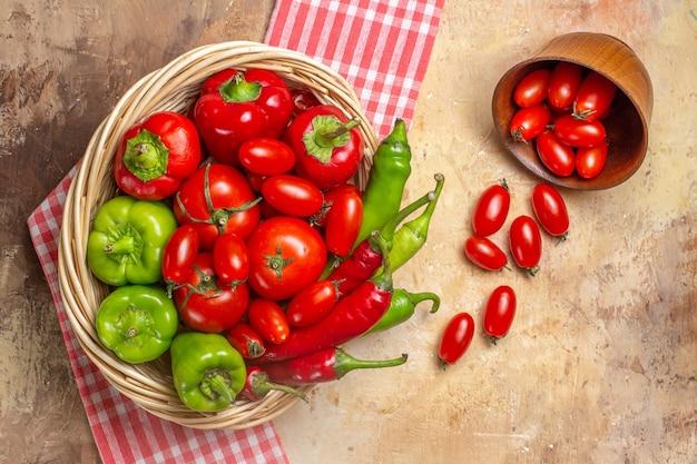 Vista superior de pimientos verdes y rojos pimientos picantes tomates en canasta de mimbre tomates cherry esparcidos de una toalla de cocina de tazón sobre fondo ámbar
