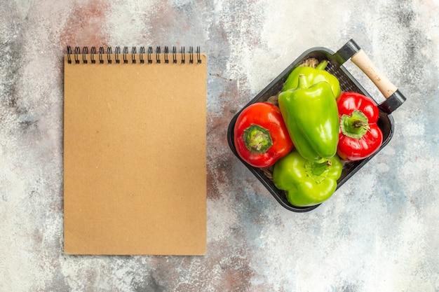 Vista superior de pimientos verdes y rojos en un tazón un cuaderno sobre una superficie desnuda