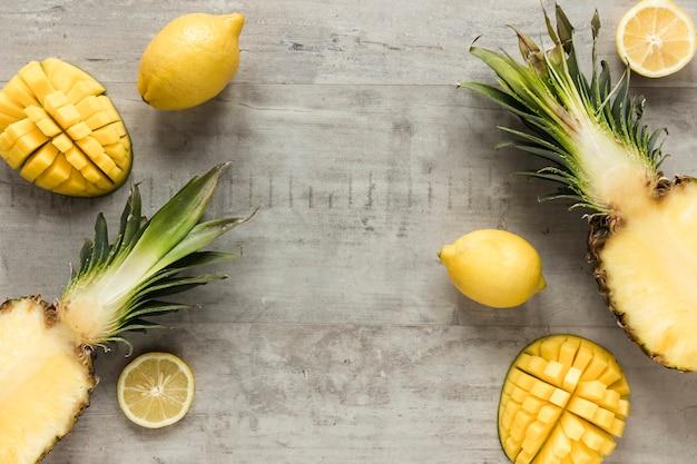 Vista superior de piña fresca con limón sobre la mesa
