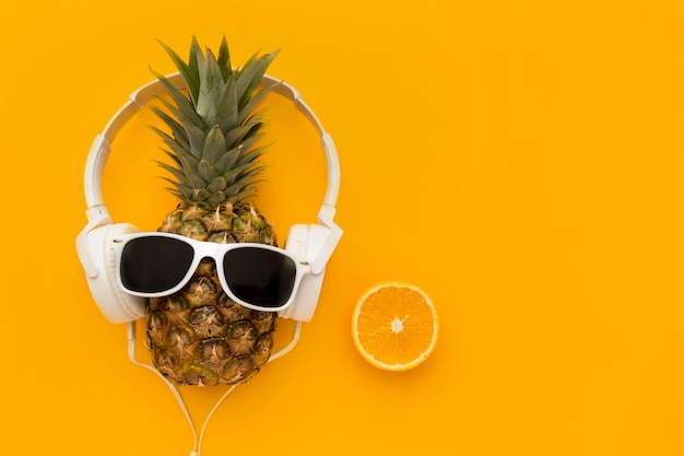 Vista superior de piña con gafas de sol y auriculares