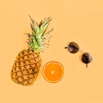 Vista superior piña, naranja y gafas de sol
