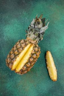Vista superior de piña con una pieza cortada de fruta entera en superficie verde