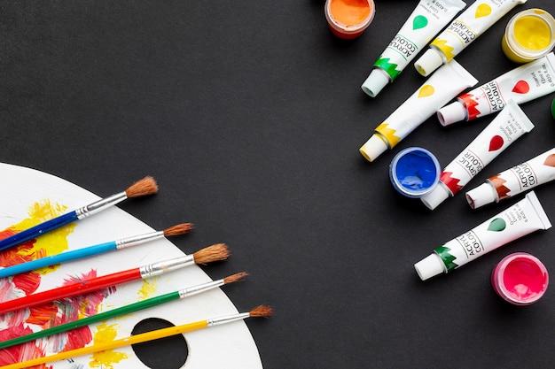 Vista superior de pincel colorido y paleta de pintura