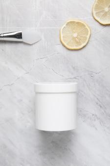Vista superior del pincel crema y rodajas de limón sobre fondo de mármol