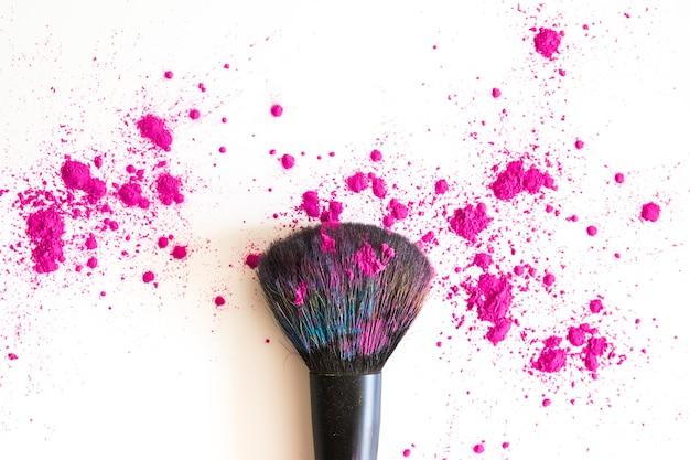 Vista superior del pincel de maquillaje y polvos rosados
