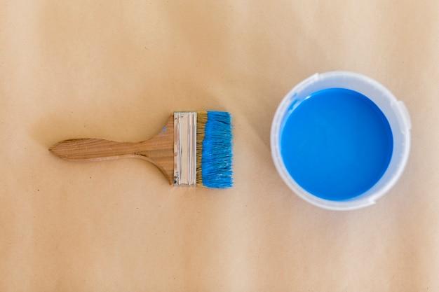 Vista superior de pintura azul y pincel