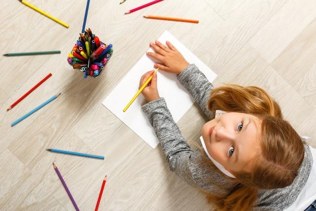 Vista superior de la pintura de la niña, mirando la cámara y sentándose en el piso.