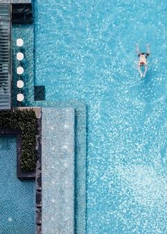 Vista superior de la piscina con barra flotante y un hombre nadando en verano.
