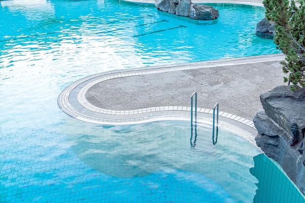 Vista superior de la piscina turquesa con pasamanos y escaleras. el concepto de verano, relajación, spa, parque acuático, arquitectura.