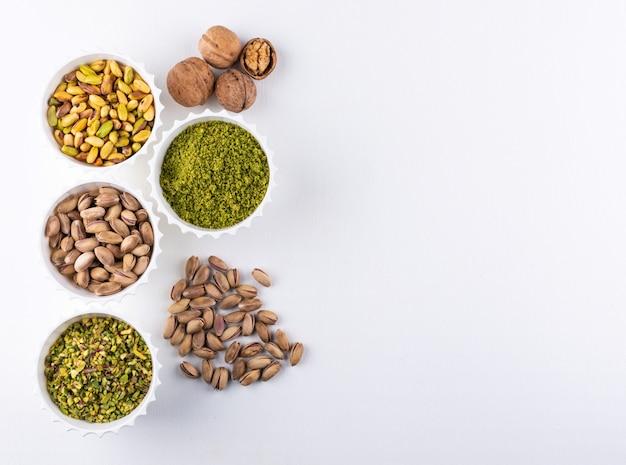 Vista superior de pistachos molidos, molidos, triturados o granulados en cuencos en blanco