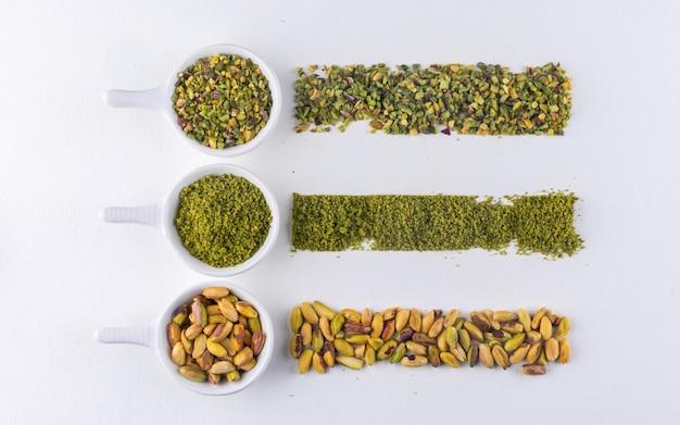 Vista superior de pistachos molidos, molidos, triturados o granulados en tazones sobre blanco