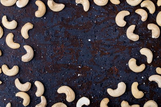 Vista superior de pistachos tostados salados aislados sobre fondo negro con espacio de copia