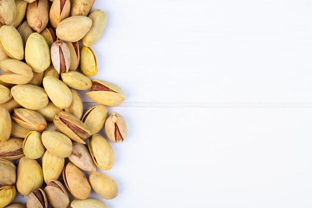 Vista superior de pistachos tostados salados sobre fondo blanco con espacio de copia