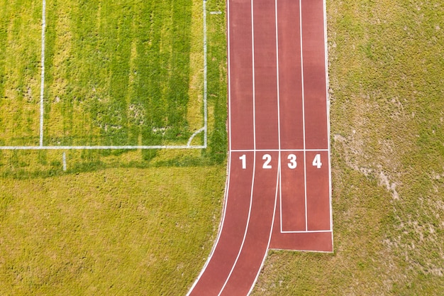 Vista superior de pistas rojas y césped de hierba verde. infraestructura para actividades deportivas.