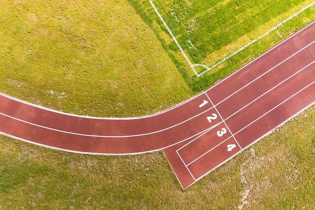 Vista superior de pistas rojas y césped verde.