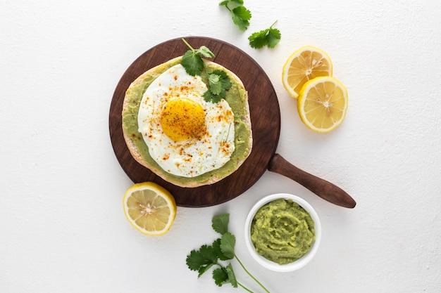 Vista superior de pita con aguacate y huevo frito en tabla de cortar