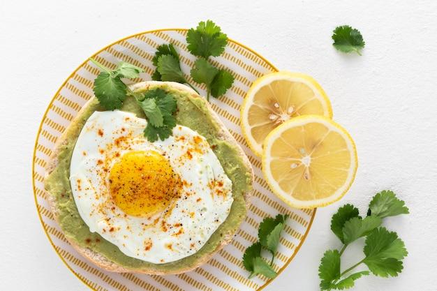 Vista superior de pita con crema de aguacate y huevo frito con rodajas de limón