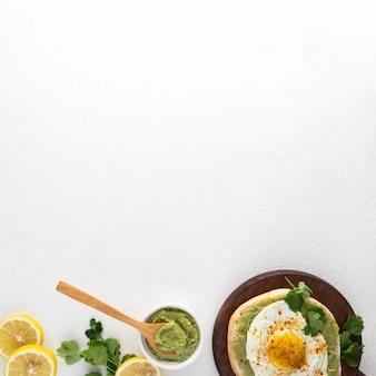Vista superior de pita con esparcimiento de aguacate y huevo frito con espacio de copia