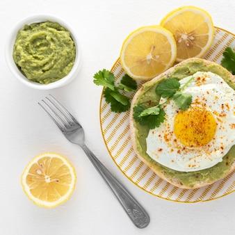 Vista superior de pita con untar de aguacate y huevo frito en un plato con un tenedor