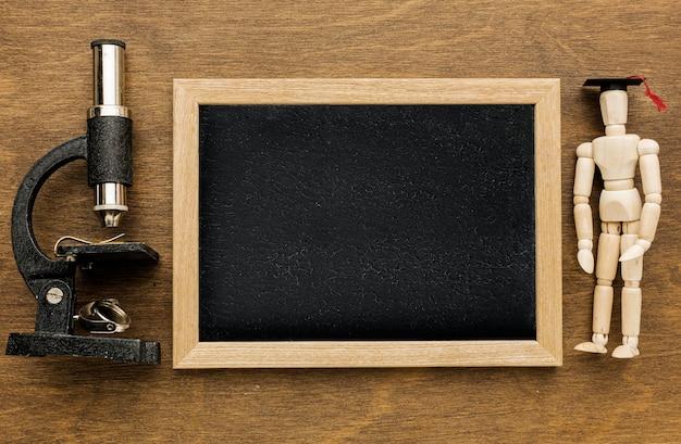 Vista superior de la pizarra con microscopio y figurilla de madera