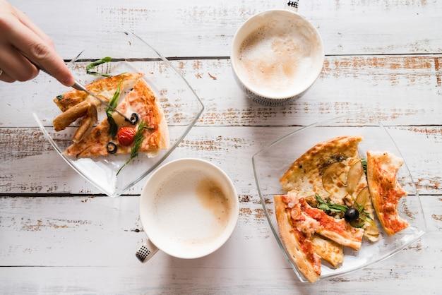 Vista superior pizza con café sobre mesa blanca